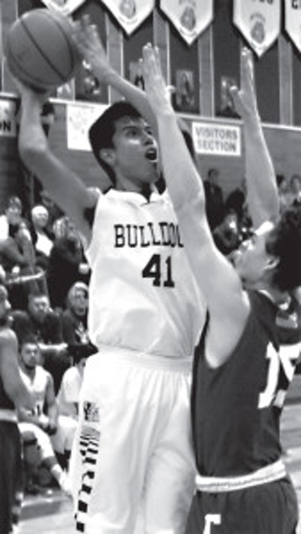 Nyssa's Andres Gonzalez puts up a shot over the outstretched arms of Colton's Mithc Nation during the third quarter of action between the two state qualifying teams.