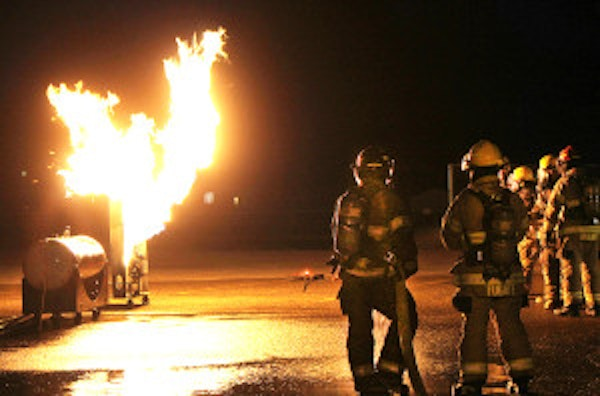 Flames flare from a gas installation used for a state firefighter safety training, as Vale Fire Department members prepare to use their skills. (Submitted photo)
