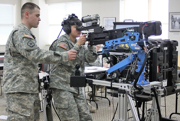 Spc. David Iveson (left) assists Pfc. Bailey Frasch during training on the M-2 .50 caliber, Unstabilized Gunnery Trainer, or UGT-I, simulator at the Baker Armoryin March. Iveson and Frasch are both assigned to Fox Company, 3rd Battalion, 116th Cavalry Regiment, Oregon Army National Guard. (Submitted by Pat Caldwell)