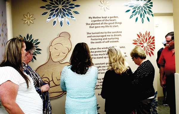 Parents and staff members read the mural message on a wall in the new maternity center at St. Alphonus in Ontario. (The Enterprise/John L. Braese)
